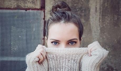 אישה מכסה את הפנים עם סוודר - עותק